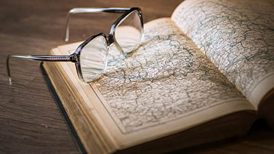 glasses and book of maps