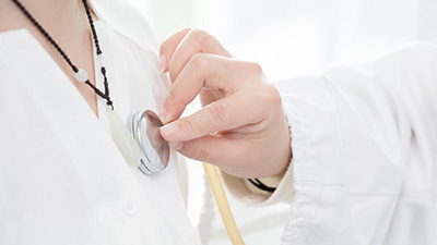 doctor holding stethoscope on patient's chest