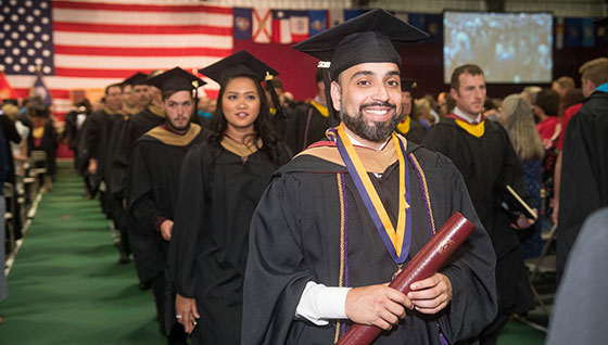 graduate holding diploma, commencement procession