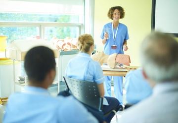 A nurse educator teaches a class to nursing students.