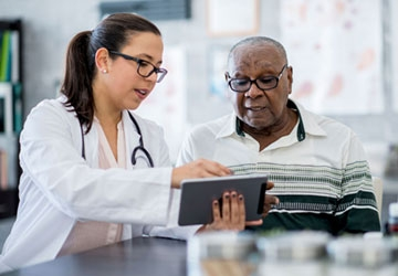 nurse leader using tablet with patient