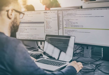 individual at computer station, three screens