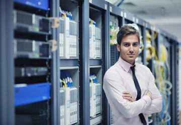 An information systems manager stands in front of a server.