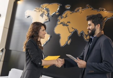 International relations professionals shake hands with a world map in the background.