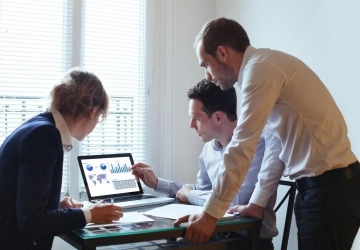 Three business professionals working together and analyzing documents and charts on a computer.