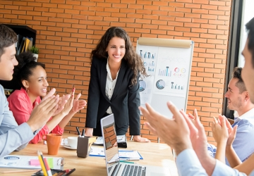 A nonprofit manager receives applause from their team after giving a presentation.