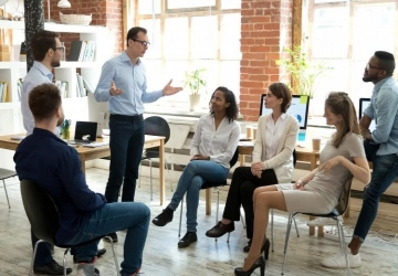 A project manager talks with employees during a meeting.