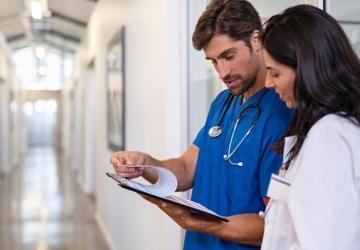 A nurse reviews a patient file with a doctor.