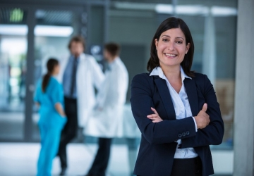 Chief nursing officer poses at her hospital with colleagues in the background