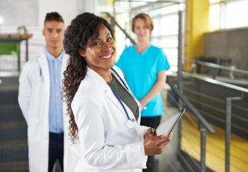 Nurse director poses alongside nurse colleagues.
