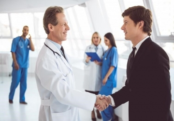 A chief quality officer shakes hands with a physician.