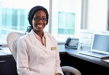 A smiling nurse practitioner sits at a desk.