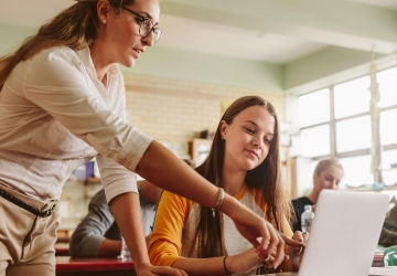 History teacher helping student in classroom