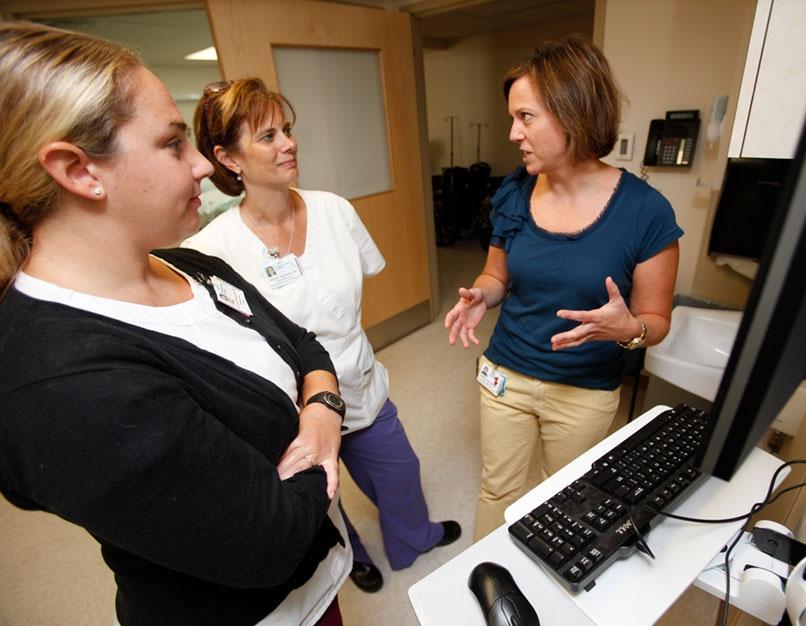 nurse leader speaking with team members