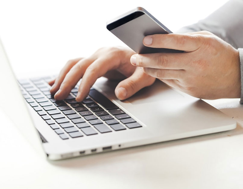 hand holding mobile device and typing on laptop