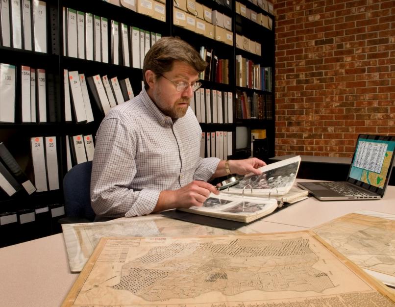 Museum curator examining archival materials.