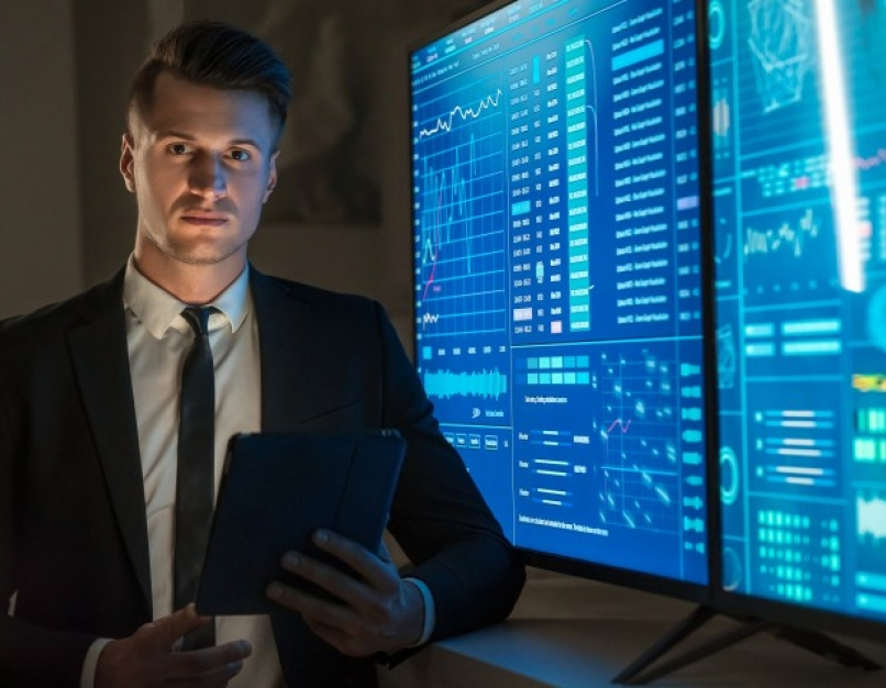 An analyst stands near computer monitors that show data.