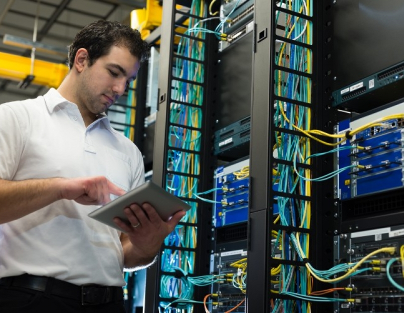 An IT technician is entering data on a tablet with network equipment and cables in the background.