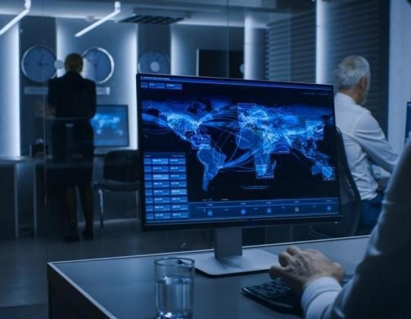 A crisis management expert analyzes global traffic on a desktop monitor.