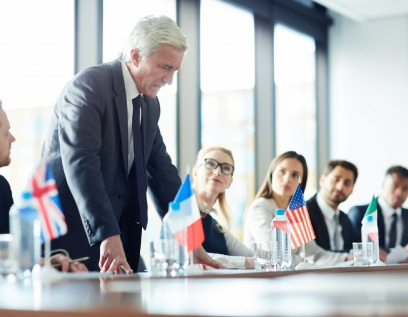 A diplomat discusses ways to improve international relations among other diplomats at a table.